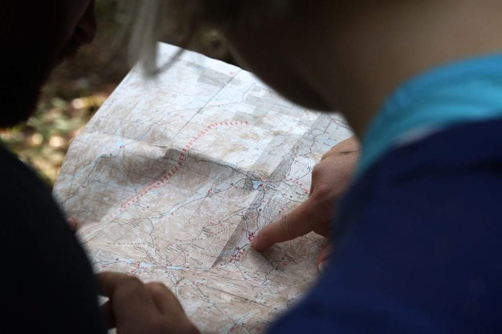 Photo of two people looking at a topographical map. The person on the right is pointing at something in the middle of the map. The background looks like they're in the woods.